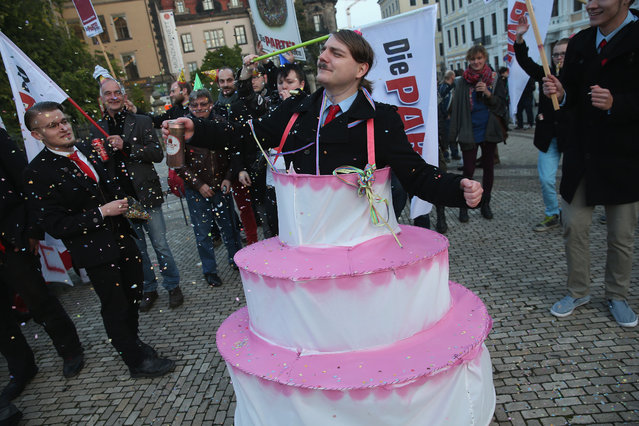 Satirical counter-demonstrators, including one dressed as Adolf Hitler and wearing a cake, pretend to celebrate the first anniversary since the first Pegida march nearby to where actual Pegida supporters were gathering on October 19, 2015 in Dresden, Germany. (Photo by Sean Gallup/Getty Images)