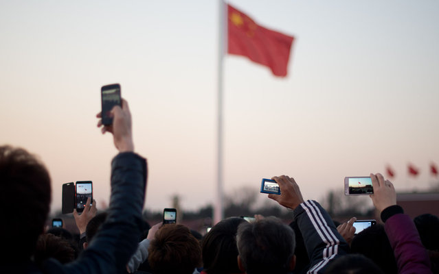 Tourists take photos during the daily flag-lowering ceremony  on Tiananmen Square in Beijing on March 4, 2013. Thousands of delegates from across China meet this week to seal a power transfer to new leaders whose first months running the Communist Party have pumped up expectations with a deluge of propaganda. (Photo by Ed Jones/AFP Photo)