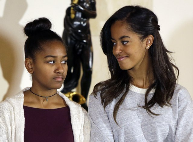 """U.S. President Barack Obama's daughters Sasha (L) and Malia listen to their father during the pardoning of the National Thanksgiving Turkey """"Cheese"""" at the White House in Washington November 26, 2014. (Photo by Gary Cameron/Reuters)"""