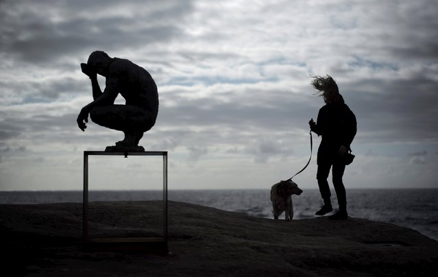 A woman takes her dog for a walk alongside British artist Laurence Edward's bronze sculpture entitled 'Crouching Man'  during the 19th annual Sculptures by the Sea exhibition in Sydney, October 23, 2015. (Photo by Jason Reed/Reuters)