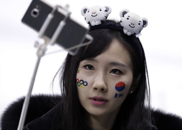 A face-painted South Korea fan take a selfie before the preliminary round of the women's hockey game between Sweden and the combined Koreas at the 2018 Winter Olympics in Gangneung, South Korea, Monday, February 12, 2018. (Photo by Julio Cortez/AP Photo)
