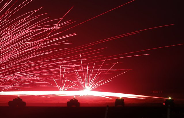 Tracer bullets ricochet off their targets as Japanese Ground Self-Defense Force tanks fire their machineguns during a night session of an annual training exercise at Higashifuji training field near Mount Fuji in Gotemba, west of Tokyo, in this August 19, 2014 file photo. (Photo by Yuya Shino/Reuters)