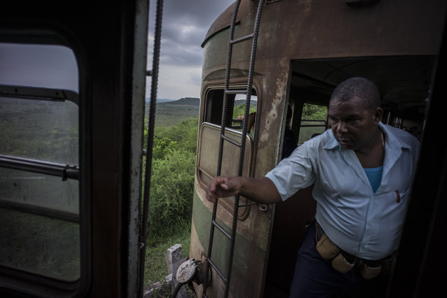 In this August 26, 2015 photo, a train conductor walks from car to car, collecting passenger tickets on the electric Hershey train as it travels toward the Casablanca municipality of Havana, Cuba. Trains connecting Cuba's capital with the former chocolate company town of Hershey in Matanzas province are filled with tourists who pay less than 50 cents for the trip as the island floods with visitors after the declaration of detente with the United States. (Photo by Ramon Espinosa/AP Photo)