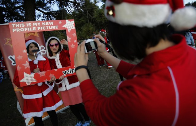 People dressed in Santa costumes pose for pictures during the Tokyo Santa Run at a park in Tokyo December 6, 2014. (Photo by Yuya Shino/Reuters)