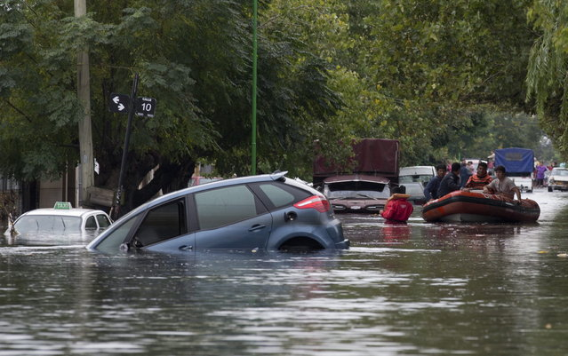 Rescue workers in a raft maneuver through a flooded street where cars are submerged along a street in La Plata, in Argentina's Buenos Aires province, Wednesday, April 3, 2013. At least 35 people were killed by flooding overnight in Argentina's Buenos Aires province, the governor said Wednesday, bringing the overall death toll from days of torrential rains to at least 41 and leaving large stretches of the provincial capital under water. (Photo by Natacha Pisarenko/AP Photo)