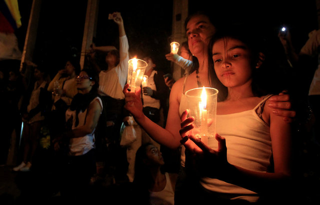 """Supporters of the peace deal signed between the government and the Revolutionary Armed Forces of Colombia (FARC) rebels holds candles during a """"Silent March"""" in Cali, Colombia, October 5, 2016. (Photo by Jaime Saldarriaga/Reuters)"""