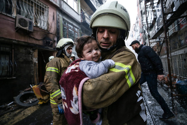 A firefighter holds a baby after she was rescued by him at the site of an explosion in natural gas pipeline during infrastructure works in Fatih district of Istanbul, Turkey on March 13, 2018. 4 people injured after the fire and initial responds were accomplished by the firefighters and health care team in the area. (Photo by Elif Ozturk/Anadolu Agency/Getty Images)