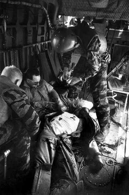 """Farley opens a first-aid kit to apply to Magel's wound as Hoilien watches Owens, the wounded gunner (with dark glasses), slumped in the rear""."