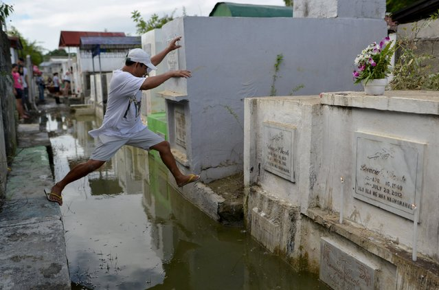 A man leaps to reach the grave of a departed loved one inside a flooded cemetery in Calumpit town, Bulacan province, north of Manila November 1, 2015. Filipinos flock to cemeteries across the country to commemorate their departed loved ones for All Saints and All Souls Days, which fall on November 1 and 2 respectively. (Photo by Ezra Acayan/Reuters)