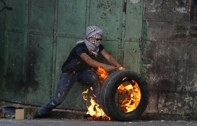 A young Palestinian protester pushes a burning tyre during clashes with Israeli troops in the West Bank city of Hebron October 31, 2015. Israeli security forces shot and killed a Palestinian who ran at them with a knife in the occupied West Bank on Saturday, police said, as a month-long wave of violence showed no signs of abating. (Photo by Ammar Awad/Reuters)