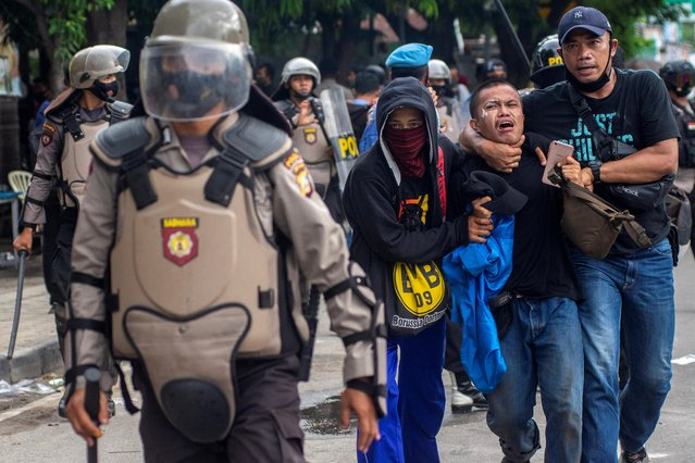 Plainclothes police officers detain a student-demonstrator during a protest against the government's labor reforms in Palu, Central Sulawesi province, Indonesia, October 8, 2020. (Photo by Basri Marzuki/Antara Foto via Reuters)
