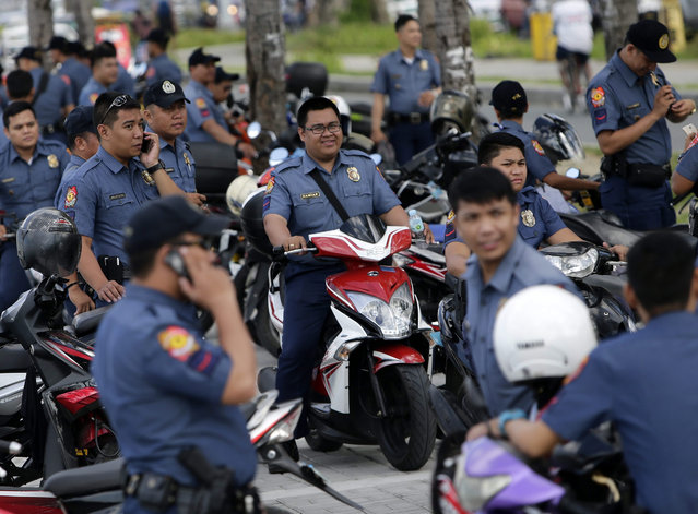 Filipino policemen gather at a street leading to the venue of the upcoming Asia-Pacific Economic Cooperation (APEC) summit in Manila, Philippines, 06 November 2015. The Philippines will hosts the meetings starting November 12, with the summit on November 18-19. President Benigno Aquino III will host a welcome dinner for the leaders of the 21 member countries on November 18. (Photo by Francis R. Malasig/EPA)
