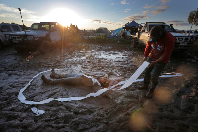 """Jess Elderedge makes a """"mud angel"""" as a friend lays toilet paper around her during a party at sunset on the final night of the Deni Ute Muster in Deniliquin, New South Wales, Australia, October 1, 2016. (Photo by Jason Reed/Reuters)"""