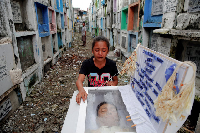 Kasandra Kate, 12, cries over the open coffin of her father Verigilio Mirano during his funeral at Navotas Public Cemetery in Manila, Philippines October 14, 2016. According to a family member, Mirano, who was using drugs but stopped after Rodrigo Duterte became the president, was killed by masked gunmen at his home on September 27th. (Photo by Damir Sagolj/Reuters)