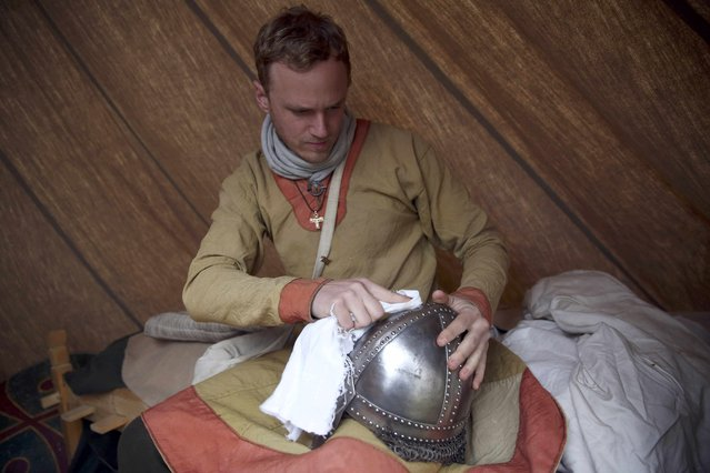 A re-enactor polishes his armour before a re-enactment of the Battle of Hastings, commemorating the 950th anniversary of the battle, in Battle, Britain October 15, 2016. (Photo by Neil Hall/Reuters)