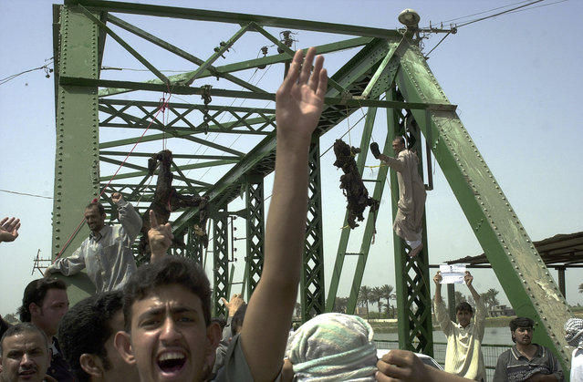 Iraqis chant anti-American slogans as charred and mutilated bodies of  U.S. contractors hang from a bridge over the Euphrates River in Fallujah, west of Baghdad, in this March 31, 2004 file photo. A lawsuit filed in 2005, filed by the families of the four slain employees of security contractor Blackwater USA, accuses the company of failing to provide the security guards with the appropriate equipment – such as armored vehicles or even a map. (Photo by Khalid Mohammed/AP Photo)