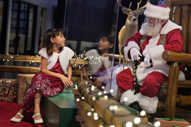 Gracelynn Blumenfeld, 8, visits with Santa through a transparent barrier at a Bass Pro Shop in Bridgeport, Conn., Tuesday, November 10, 2020.  Malls are doing all they can to keep the jolly old man safe from the coronavirus, including banning kids from sitting on his knee, completely changing what a Santa visit looks like. (Photo by Seth Wenig/AP Photo)