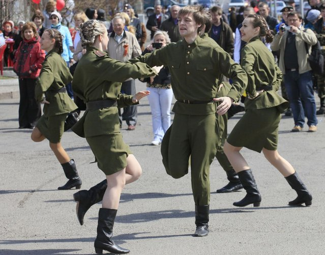 Youths dressed in Red Army uniforms participate in a street performance ahead of Victory Day in the Russian Siberian city of Krasnoyarsk, May 7, 2013. Russia marks its victory over Nazi Germany in World War Two every year on May 9. (Photo by Ylia Naymushin/Reuters)