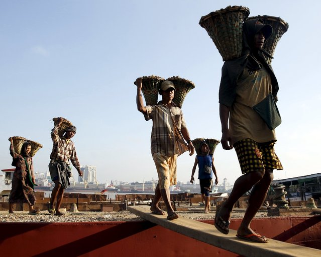 Labourers unload gravel from a boat docked in Dala township, opposite Yangon city, Myanmar, November 12, 2015. (Photo by Olivia Harris/Reuters)