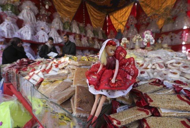"A man sells traditional doll toys and sweets for children to celebrate the birthday of prophet Muhammad, also known as ""mawlid al nabi"", which will fall next week, in a makeshift tent in Cairo, December 30, 2014. (Photo by Mohamed Abd El Ghany/Reuters)"