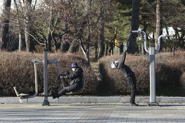 People wearing face masks as a precaution against the coronavirus exercise at a park at a park in Goyang, South Korea, Friday, December 4, 2020. The Korea Disease Control and Prevention Agency said Friday that 600 of the newly confirmed patients were domestically transmitted cases – nearly 80% of them in the densely populous Seoul area, which has been at the center of a recent viral resurgence. (Photo by Ahn Young-joon/AP Photo)