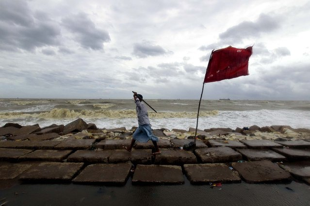 A volunteer walks along the Bay of Bengal coast to evacuate people in Chittagong, Bangladesh, on May 16, 2013. Cyclone Mahasen struck the southern coast of Bangladesh on Thursday, lashing remote fishing villages with heavy rain and fierce winds that flattened mud and straw huts and forced the evacuation of more than 1 million people. (Photo by A. M. Ahad/Associated Press)
