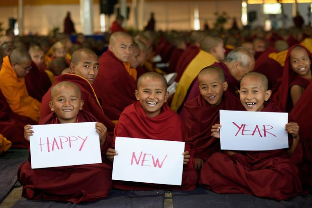 """Novice Buddhist monks smile as they pose with Happy New Year placards during """"kagyu monalm"""" prayers at Bodhgaya on January 1, 2015. (Photo by AFP Photo)"""