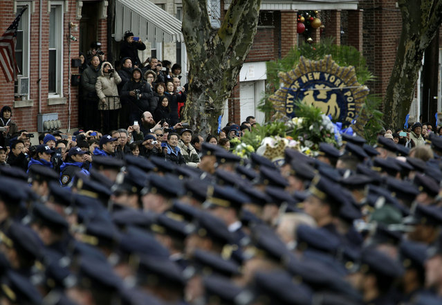 Spectators watch as the funeral procession for Officer Wenjian Liu passes in the Brooklyn borough of New York, Sunday, January 4, 2015. (Photo by Seth Wenig/AP Photo)