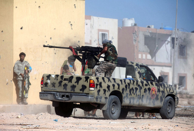 A member of Libyan forces allied with the U.N.-backed government fires a weapon on a pickup truck during a battle with Islamic State militants in Giza Bahreya, in Sirte, Libya October 27, 2016. (Photo by Hani Amara/Reuters)