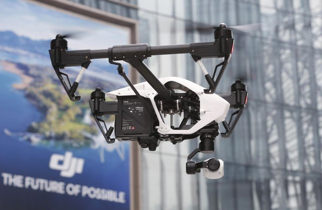In this Monday, December 15, 2014 photo, a DJI Technology Co.'s Inspire 1 drone flies against the backdrop of a DJI's advertisement board during a demonstration in Shenzhen, south China's Guangdong province. Founded in 2009 by an engineer with a childhood love of radio-controlled model planes, DJI has become the leading supplier in the fast-growing market for civilian drones – possibly the first Chinese brand to achieve No. 1 status in a global consumer product. (Photo by Kin Cheung/AP Photo)