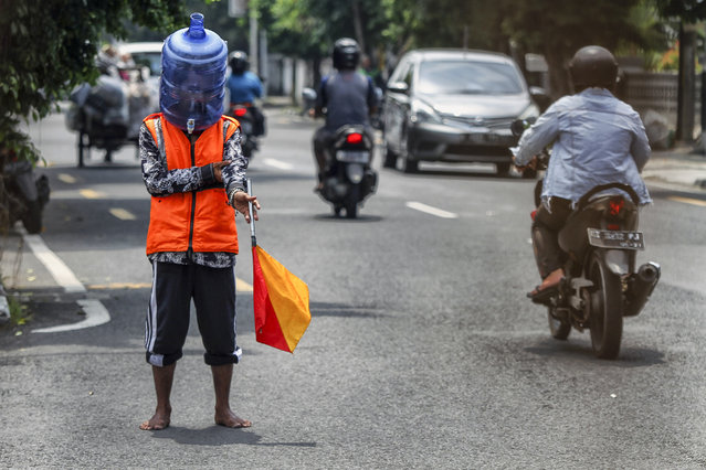 A resident uses face shields made from used mineral water containers while working on the streets of Yogyakarta City, Indonesia on April 16, 2020. This face shield aims to prevent contracting from coronavirus while working outside the home. (Photo by Nuryanto/Opn Images/Barcroft Media via Getty Images)