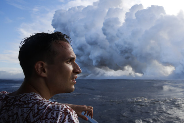 Gabor Kovacs, visiting from Hungary, watches as lava flows into the ocean, generating plumes of steam, near Pahoa, Hawaii Sunday, May 20, 2018. Kilauea volcano that is oozing, spewing and exploding on Hawaii's Big Island has gotten more hazardous in recent days, with rivers of molten rock pouring into the ocean Sunday and flying lava causing the first major injury. (Photo by Jae C. Hong/AP Photo)