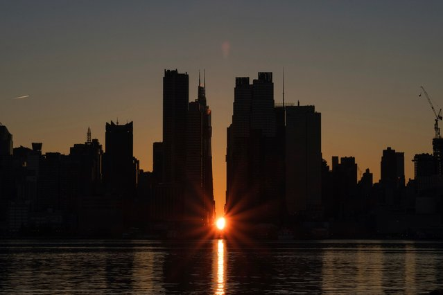 The sun rises through the middle of buildings long 42nd street in New York's Manhattan borough during a phenomenon known as Manhattanhenge on Sunday, November 29, 2020, as viewed from Weehawken, N.J. Manhattanhenge is when the rising sun intersects with the Manhattan street grid. (Photo by Yuki Iwamura/AP Photo)