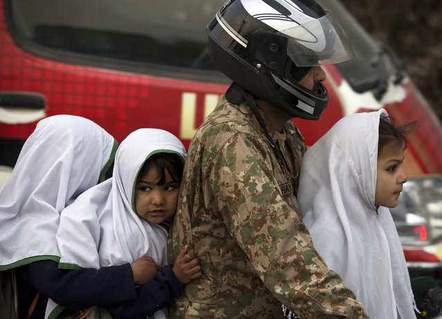 A Pakistan army soldier transport his children to a school near the Army Public School targeted by Taliban militants, in Peshawar, Pakistan, Monday, January 12, 2015. Pakistani children and their parents returned Monday to the school where Taliban gunmen killed 150 of their classmates and teachers. (Photo by B.K. Bangash/AP Photo)