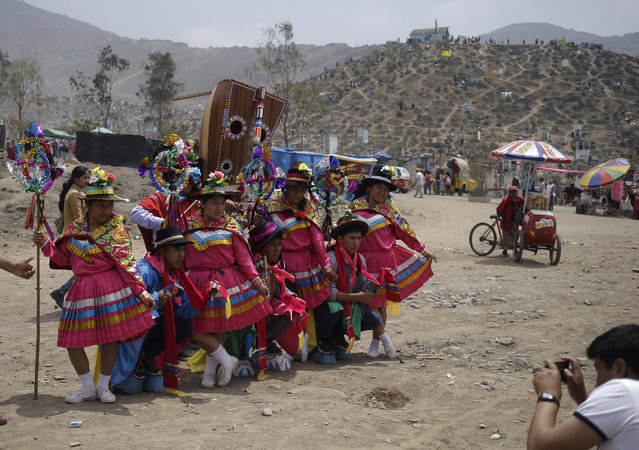 A group of dancers pose for a photo before their performance at the Nueva Esperanza cemetery in the shantytown Villa Maria, in Lima, Peru, Tuesday, November 1, 2016, as part of the Day of the Dead festivities. The holiday honors the deceased and coincides with All Saints Day, and All Souls Day celebrated on Nov. 1 and 2. Dancing, drinking alcohol, and eating with the deceased are part of Day of the Dead celebrations. (Photo by Martin Mejia/AP Photo)