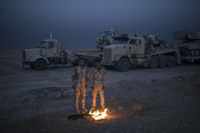 Iraqi army soldiers warm themselves next to a fire near the Qayara air base, south of Mosul, Iraq, Tuesday, November 1, 2016. The U.N. human rights office is lauding efforts by the U.S.-led coalition in the battle against the Islamic State group in Mosul. The office in Geneva says coalition flights over Iraq have largely succeeded in preventing IS from bringing in 25,000 more civilians to the city center, where the militant group has been using people as human shields as Iraqi forces advance on Mosul. (Photo by Felipe Dana/AP Photo)
