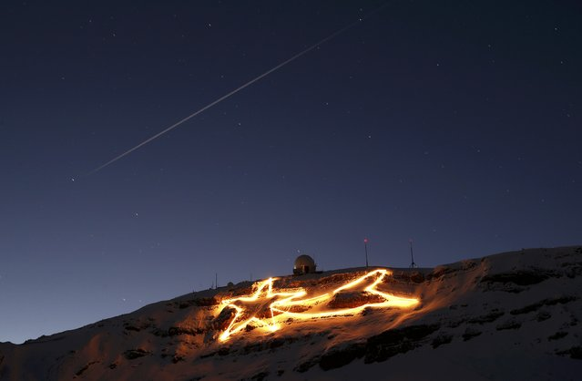 A Christmas decoration representing a shooting star is pictured under the Dole summit in Cheserex, Switzerland December 1, 2015. The installation, 160m wide and 75m high with a linear length of about 800m, is attached every summer to the rocks under the radar station on top of the Dole summit (1677m - 5500 ft) by its instigator Stephane Richard and a team of 20 volunteers. (Photo by Denis Balibouse/Reuters)