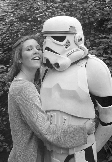 "American actress Carrie Fisher, star of the movie ""The Empire Strikes Back"", sequel to the record-breaking ""Star Wars"" epic, cuddles up to a Stormtrooper in a London park, May 23, 1980. They were in London to promote the movie. (Photo by Dave Caulkin/AP Photo)"