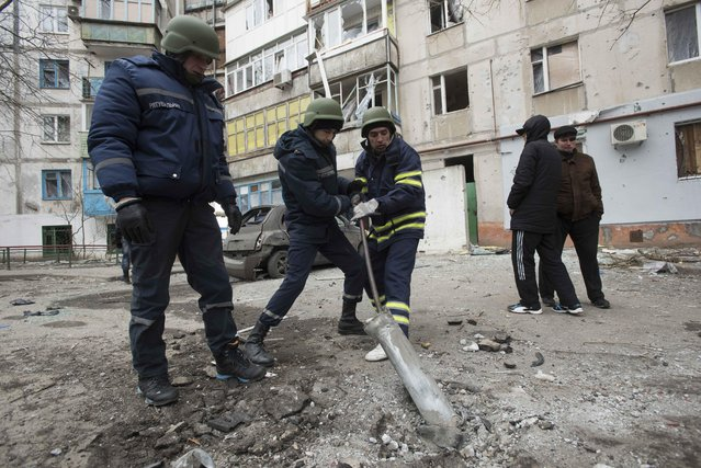 Rescue workers try to pull out a piece of an exploded Grad missile outside an apartment building in Vostochniy district of Mariupol, Eastern Ukraine, Sunday, January 25, 2015. Indiscriminate rocket fire slammed into a market, schools, homes and shops Saturday in Ukraine's southeastern city of Mariupol. (Photo by Evgeniy Maloletka/AP Photo)