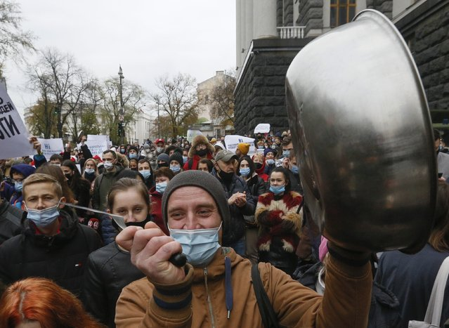 Workers of restaurant businesses bang on pans in a sign of protest against the newly introduced coronavirus weekend quarantine in front of the Cabinet in Kyiv, Ukraine, Wednesday, November 11, 2020. Ukraine's Cabinet has ruled to introduce a weekend quarantine, allowing to work only food stores, pharmacies, public transport and gas stations in an attempt to fight against raising COVID-19 cases in Ukraine. (Photo by Efrem Lukatsky/AP Photo)