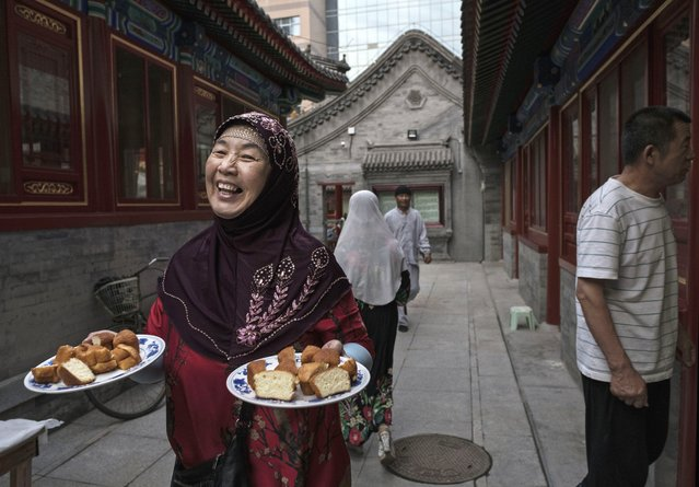 A woman from the Hui Muslim community carries food that will be eaten by her and others to break their fast during the holy fasting month of Ramadan at the Nanxiapo Mosque on June 8, 2018 in Beijing, China. (Photo by Kevin Frayer/Getty Images)