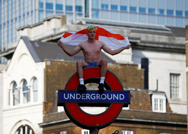 England fan celebrates on top of an Underground tube sign after England' s win over Sweden in the Russia 2018 World Cup quarter- final football match, in London on July 7, 2018. (Photo by Henry Nicholls/Reuters)