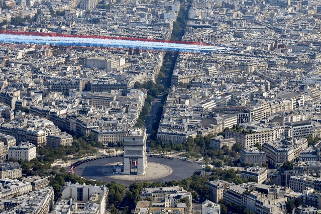 The Patrouille de France Alpha Jet aircrafts fly over the Arc de Triomphe at the start of the annual Bastille Day military parade on the Champs-Elysees avenue in Paris on July 14, 2018. There were two minor glitches: one of the planes in the flypast supposed to be leaving the blue, white and red colours of the national flag in their trail spread a line of red instead of blue and two motorbike-riding gendarmes fell off after a minor collision. (Photo by Gerard Julien/AFP Photo)