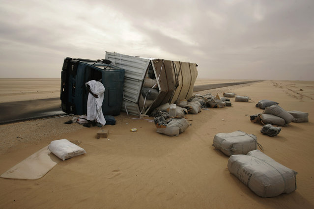 A man looks inside an overturned truck after an accident along the road between Nouahibou and Nouakchott, Mauritania December 3, 2009. (Photo by Rafael Marchante/Reuters)