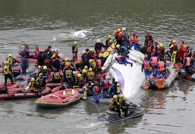 """Rescuers carry out rescue operations after a TransAsia plane crashed into a river in New Taipei City, February 4, 2015. One person was killed but another 10 showed """"no sign of life"""" after the TransAsia plane carrying 58 passengers and crew crashed into a river in downtown Taipei shortly after take-off, Taiwan's fire department said on Wednesday. (Photo by Pichi Chuang/Reuters)"""