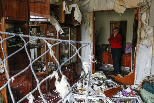 A woman reacts as she looks at the debris inside a flat at a residential block damaged by a recent shelling in Yenakieve town, northeast from Donetsk, February 2, 2015. (Photo by Maxim Shemetov/Reuters)