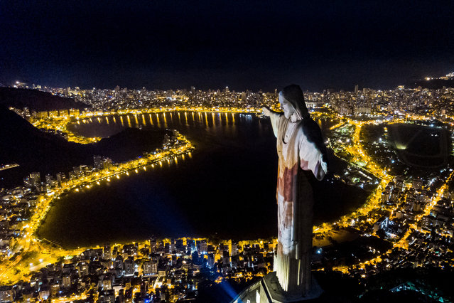 Aerial view of the illuminated statue of Christ the Redeemer in a honor of the medical workers amidst the Coronavirus (COVID-19) pandemic on December 31, 2020 in Rio de Janeiro, Brazil. The city of Rio de Janeiro decided to close the beaches to avoid crowds due to the coronavirus (COVID-19) pandemic. Sound equipment, car parking, beach vendors and fireworks have been prohibited on the shore at the turn of the year. About 10,000 military police officers and teams from the Municipal Guard will act to try to maintain order. (Photo by Buda Mendes/Getty Images)