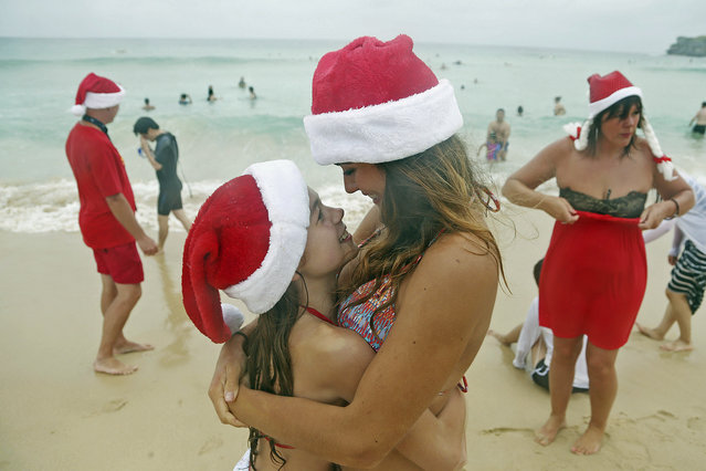Lucy O'Grady, center right, hugs her little sister Poppie O'Grady, to keep her warm as the visitors from Birmingham in the United Kingdom celebrate Christmas Day at Bondi Beach in Sydney, Wednesday, December 25, 2013. (Photo by Rick Rycroft/AP Photo)