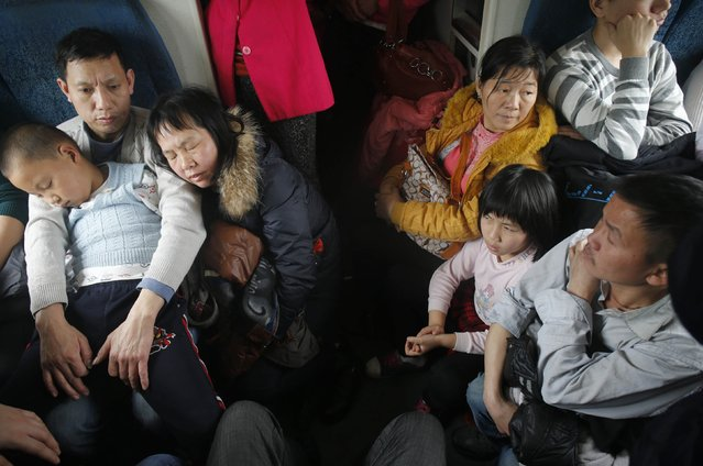 Passengers sit and stand in the corridor of a train, set aside exclusively for migrant workers travelling from Guangzhou of Guangdong province to Wuhan of Hubei province, February 7, 2015. (Photo by Reuters/Stringer)