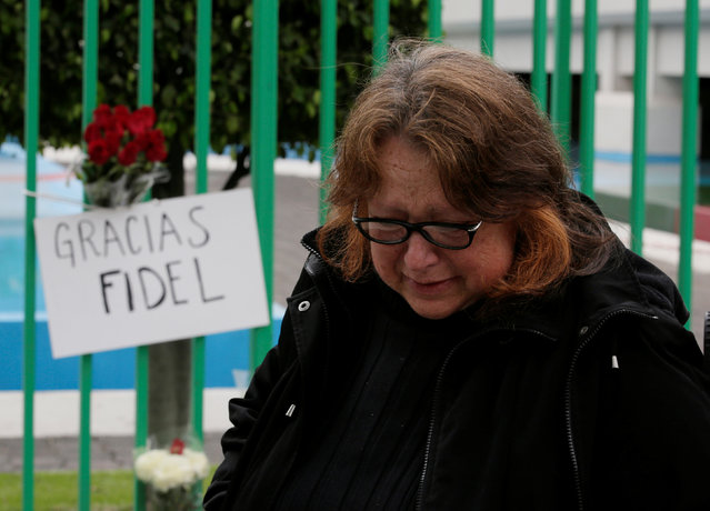 """A woman reacts next to a placard and flowers as part a tribute outside the Cuban Embassy in Mexico, following the announcement of the death of Cuban revolutionary leader Fidel Castro, in Mexico City, Mexico November 26, 2016. The placard reads: """"Thanks, Fidel"""". (Photo by Henry Romero/Reuters)"""